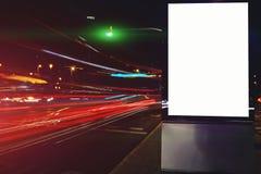 外面社会信息委员会在晚上,给横幅的嘲笑做广告与在背景的被弄脏的光 库存照片