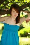 外面青少年的女孩由结构树 库存照片