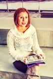 外面年轻美国妇女读书 免版税库存照片