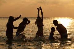 多一代家庭剪影获得乐趣在海 库存照片