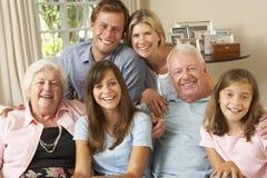 多一代家庭小组坐沙发户内 库存照片