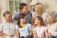 多一代家庭小组坐沙发户内 免版税图库摄影
