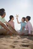 多世代家庭坐看海星的海滩 免版税图库摄影