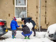 多云冬日观点的做雪人的家庭母亲和两个男孩在典型的多雪的英国路小径之间 免版税库存图片
