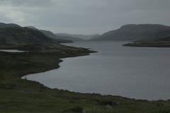 多云多雨惨淡的风景有湖和山的看法 免版税库存图片