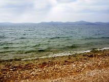 多云天和Pebble海滩 免版税图库摄影