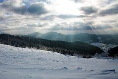 多云天空和太阳射线山的冬天森林 免版税图库摄影