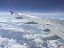 多云天空和翼在平面` s窗口 免版税库存照片