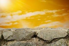 多云天空日落和石墙背景 免版税库存照片