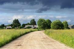 黑多云天空背景的小村庄 免版税库存图片
