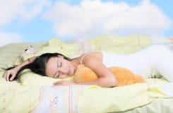 多云天空背景的睡觉的少妇 免版税库存照片