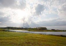多云太阳和天空在高尔夫球场 免版税图库摄影
