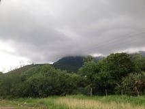 多云的小山和太阳绿色 免版税库存图片