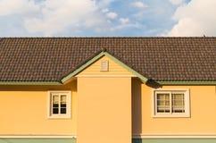 多云蓝天的黄色房子 库存图片