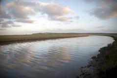 多云阴暗天空和一条河日出的 免版税库存照片