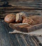多五谷小圆面包的分类在老木桌上 库存照片