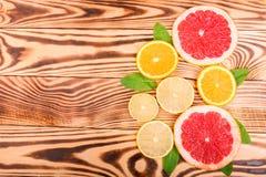 多五颜六色的切片新鲜的橙色,水多的柠檬和成熟葡萄柚与绿色叶子在一张浅褐色的木桌,顶视图上 库存照片