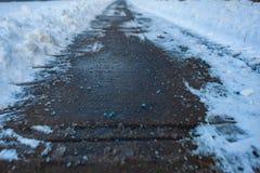 多伦多,加拿大- 2019年1月27日:在路的加拿大蓝色盐好熔化的与液体镁氯化物的冰 库存图片