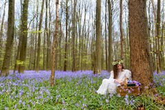维多利亚女王时代的妇女在会开蓝色钟形花的草森林里 免版税库存图片