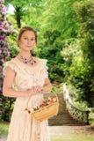 维多利亚女王时代的妇女在有玫瑰的庭院里 免版税库存图片