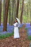 维多利亚女王时代的礼服在会开蓝色钟形花的草森林里 免版税库存图片