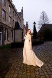 维多利亚女王时代的礼服的妇女在晚上走的一个老城市广场 库存照片