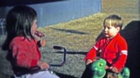 维多利亚, BC - 1972年:分享棒棒糖的大姐与她爱的她的弟弟 股票录像