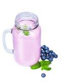 从水多和新鲜的蓝莓的可口桃红色圆滑的人在金属螺盖玻璃瓶和甜莓果堆与鲜绿色的叶子的 免版税库存照片
