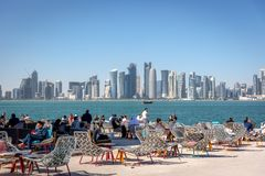 多哈、卡塔尔- 2018年1月8日-享用与多哈` s地平线的本机和游人一个咖啡馆酒吧在背景中在一蓝天天, C大调的第1音 图库摄影