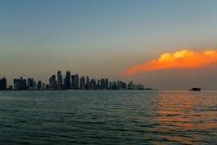 多哈,卡塔尔:在城市地平线的一朵美丽的日落云彩 图库摄影