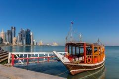 多哈,卡塔尔- 2018年1月8日-橙色传统驾驶的小船等待的游人在多哈` s街市在一蓝天天 免版税库存图片
