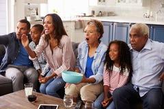 多在电视的一代黑色家庭观看的体育在家 免版税库存图片