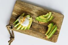 多士、avacado三明治和荷包蛋在一块木砧板 库存照片
