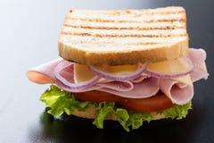 多士在黑桌上的火腿三明治 库存图片