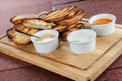 多士烤面包的切片用乳酪和芝麻在一个木板的一个调味汁滑倒了 图库摄影