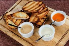 多士烤面包的切片用乳酪和芝麻在一个木板的一个调味汁滑倒了 免版税图库摄影