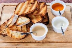 多士烤面包的切片用乳酪和芝麻在一个木板的一个调味汁滑倒了 库存照片