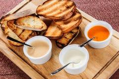 多士烤面包的切片用乳酪和芝麻在一个木板的一个调味汁滑倒了 免版税库存图片