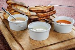 多士烤面包的切片用乳酪和芝麻在一个木板的一个调味汁滑倒了 库存图片