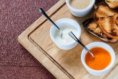 多士烤面包的切片用乳酪和芝麻在一个木板的一个调味汁滑倒了 免版税库存照片