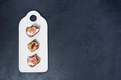 多士用在一块白色砧板的帕尔马、蒜味咸腊肠和鹅头脑 免版税库存照片
