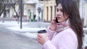 多孔的通信、可爱的妇女谈话在手机和饮用的茶,当走在城市时 影视素材