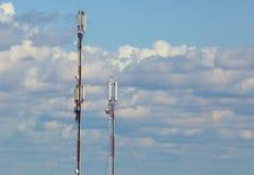 多孔的通信两个塔关于多云天空的背景的 库存图片