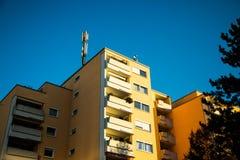 多家庭房子在慕尼黑,黄色门面,蓝天,流动收音机的天线在屋顶 免版税库存照片