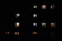 多层的大厦有启发性窗口在晚上 图库摄影