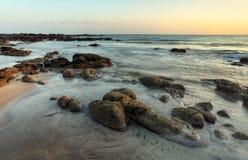 多岩石的海滩在低潮揭露了在平衡日落以后 免版税库存图片