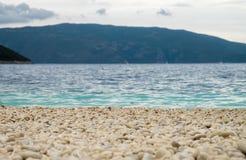 多岩石的海滩、海、山和天空 免版税库存图片