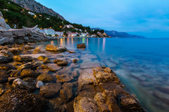 多岩石的海滩和小村庄在Omis附近在晚上 库存照片