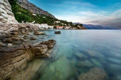 多岩石的海滩和小村庄在Omis附近在黄昏 库存照片
