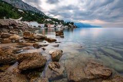 多岩石的海滩和小村庄在Omis附近早晨 免版税库存照片